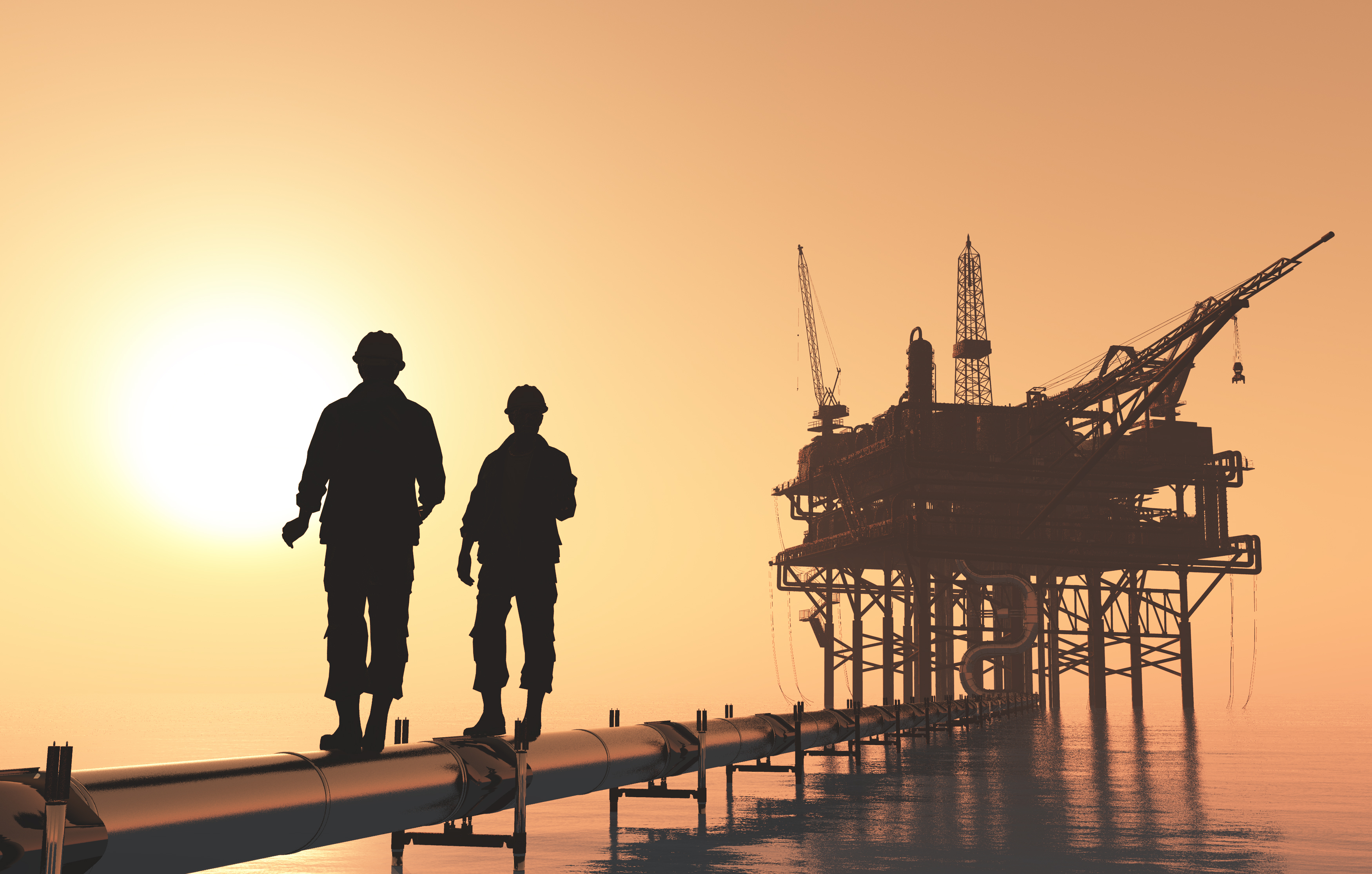 silhouettes of workers wearing hard hats walking on a pipe above water in front of an oil rig with the sun behind them